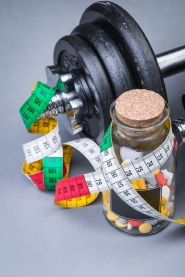 bottle of diet pills with measuring tape